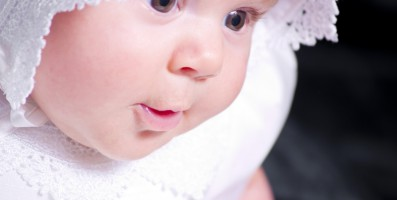 A portrait of a baby girl in a christening dress on a dark background. This photo has a shallow depth of field and the focus is on her eye.